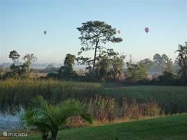 Dit uitzicht heeft u rechts vanuit het zwembad en terras. Regelmatig worden er ballon vaarten gedaan die dan over het meer gaan.