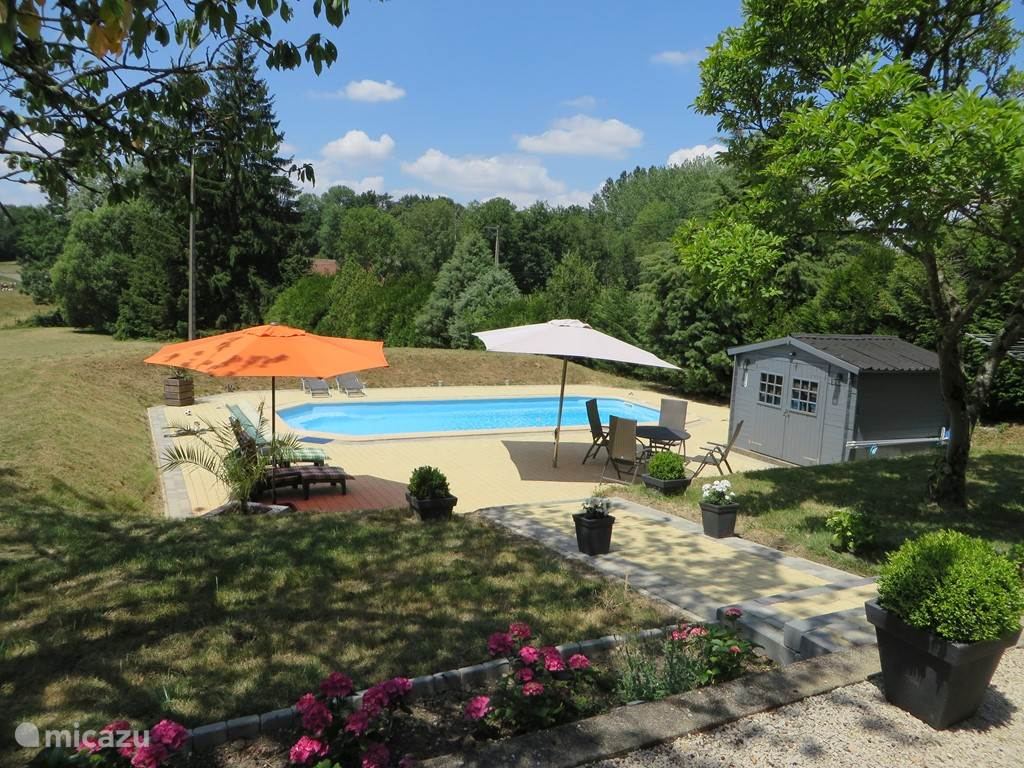 Uitzicht vanuit het huis naar het zwembad en terras. Vanuit het huis kan u direct naar het zwembad lopen. Het zwembad ligt geheel omsloten in de tuin en biedt u maximale privacy. Er staan ligbedden en een tafel met verstelbare stoelen om lekker te kunnen lunchen of dineren.