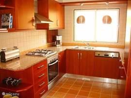 Moderne keuken van alle comfort voorzien; afwasmachine, wasmachine, magnetron, broodrooster, oven en koffiezetapparaat en waterkoker