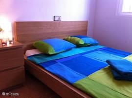 Slaapkamer eerste verdieping voor 2 personen met nachtkastje,lamp en ingebouwde kast.