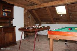 The large playroom with billiards, shuffleboard, foosball, TV-video plus cabinet with various games.