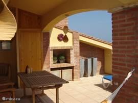 halfoverdekt terras van 35 m2, met oa eettafel, ligbedden en barbecue
