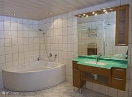 De luxe badkamer, heerlijk ruim en smaakvol ingericht met kersenhouten meubels. Zo mooi benoemd door 1 van onze gasten, de badzáal! Een ruim bad en een mooi badmeubel maken de badkamer tot een waar paradijs. In de badkamer vindt u ook een zeer grote seperate douche met rainshowerdouchekop.
