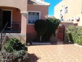 De tuin met aan de linkerzijde een sinaasappelboompje