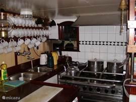 Aan het dagverblijf de open keuken; 6 pits gasfornuis met gasoven, vaatwasser, koelkast ( de 2e en vriezer in dames wasruimte)