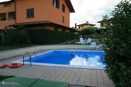 Het ruime zwembad ligt langs de tuin. Vanaf de woning heb je een goed zicht over het zwembad.