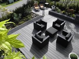Een ruim terras met 4 relax stoelen en 2 ligbedden