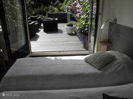 The bedroom on the ground floor with patio doors to the terrace
