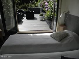 De slaapkamer op de begane grond met openslaande deuren naar het terras