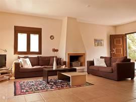 Gezellige woonkamer met openhaard, flatscreen, Dvd-speler en uitkijk over groen en zee!