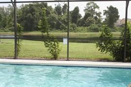 Vanuit het zwembad uitzicht op het meertje achter de Villa.