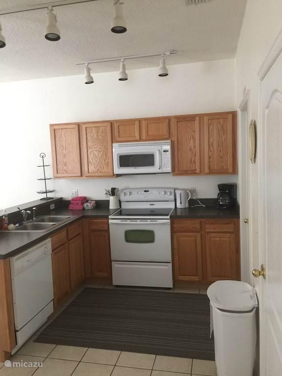 Keuken met kookstel, oven, microwave, koelkast, vaatwasser, borden en kommen, bestek
