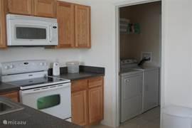 Keuken en bijkeuken met wasmachine en droger.