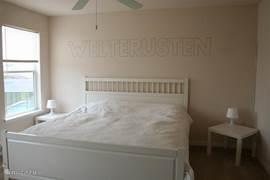 Welterusten-kamer met Kingsize bed, TV en uitzicht op het (verwarmd) privé zwembad.