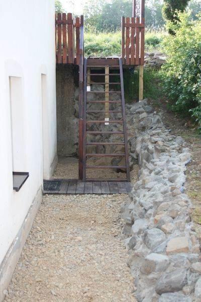 Door de deur vanuit de keuken loopt u buitenom via deze trap naar het achterterras.