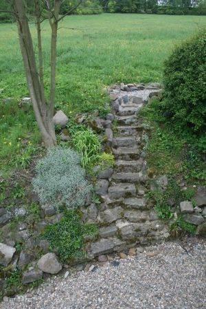 Authentieke stenentrap van waar u linksom (vanaf balkon/garagekant) het achterterras kan bereiken.