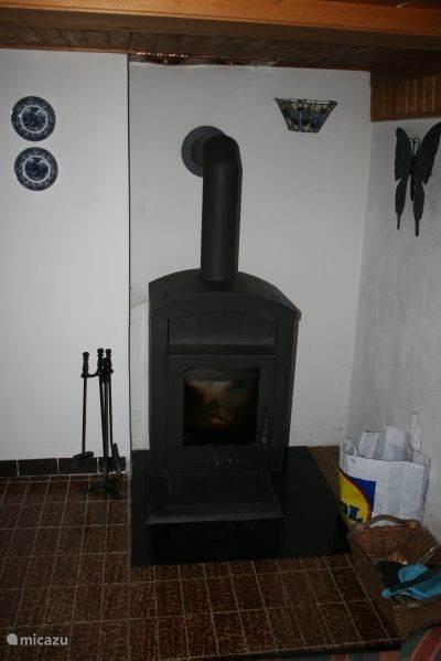 Functionele Tsjechische houtkachel in de huiskamer voor behaaglijke warmte. Er ligt voldoende open haard hout in een houthok achter het huis. In de gang staat ook zo'n kachel voor warmte in het hele huis.