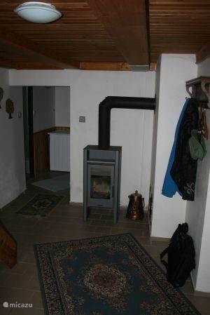 Hal beneden met comfortabele recent geplaatste houtkachel.Links van de kachel in de hoek een degelijke Bosch wasmachine.
