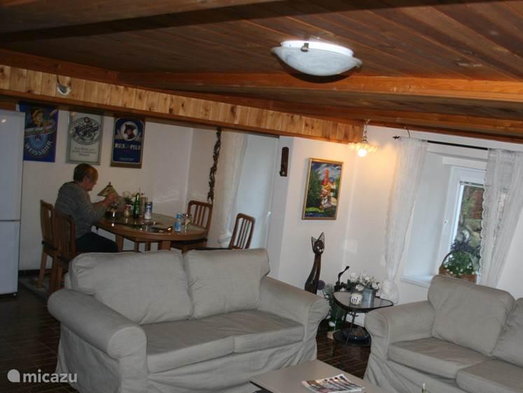 Overgang woonkamer naar eetkamer en keuken. De stahoogte is 210 centimeter. Het huis is geschikt voor lange mensen alleen even bukken van woonkamer naar keuken. Apart eetgedeelte in huiskamer met uitschuifbare tafel voor 8 personen. Aan de muur boven u 3 authentieke emaille platen van Duitse biermer