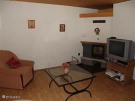Woonkamer met houtkachel, tv, DVD-speler en WII