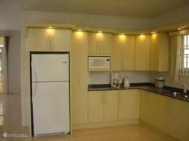 Keuken, met koelkast en magnetron.