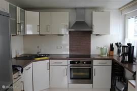 Onze moderne keuken met apparatuur zoals een oven, afzuigkap, koelkast en vrieskast en uiteraard een vaatwasser. Koken gaat op inductie. De speciale pannen staan in de keukenkastjes.