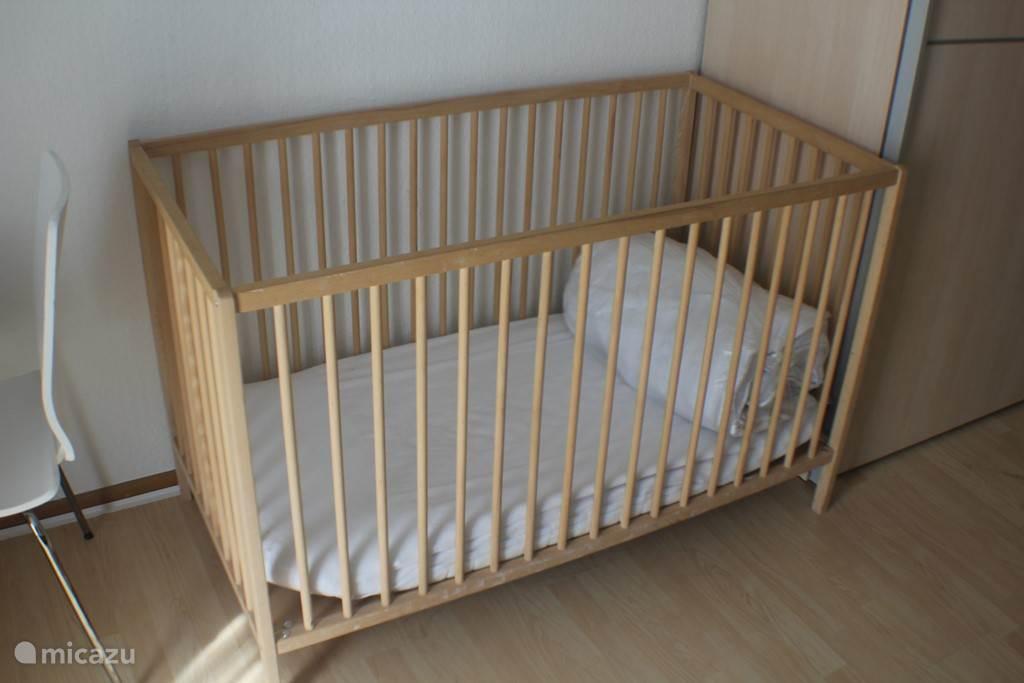 Op twee slaapkamers staat een kinderledikantje met een matrasje.