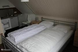 Slaapkamer 6.  Op deze slaapkamer staat een tweepersoons bed (2. x 1.60 m) met eenpersoons matrassen en dekbedden. Op de achtergrond ziet u nog een keukenblok met warm en koud stromend water.