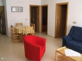 ruime woon- en eetkamer met zit- en eethoek, airconditioning, plafondventilator en twee verplaatsbare convectorkachels;  toegang naar slaapkamers en badkamer