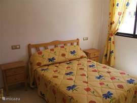 slaapkamer met 2-persoonsbed en met linnenkast (schuifdeuren) over de gehele breedte van de kamer, schuiframen en rolluik, plafondventilator en verplaatsbare ventilator