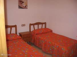 slaapkamer met twee 1-persoons-bedden, ruime linnenkast, schuiframen en rolluik, plafondventilator verplaatsbare ventilator