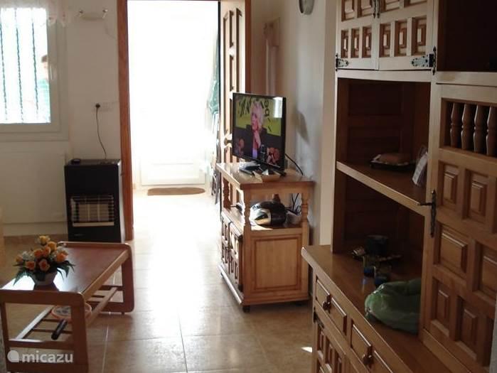 woonkamer met gaskachel, tv, radio/cd-speler en wandkast. doorkijk naar voorkamer met eethoek