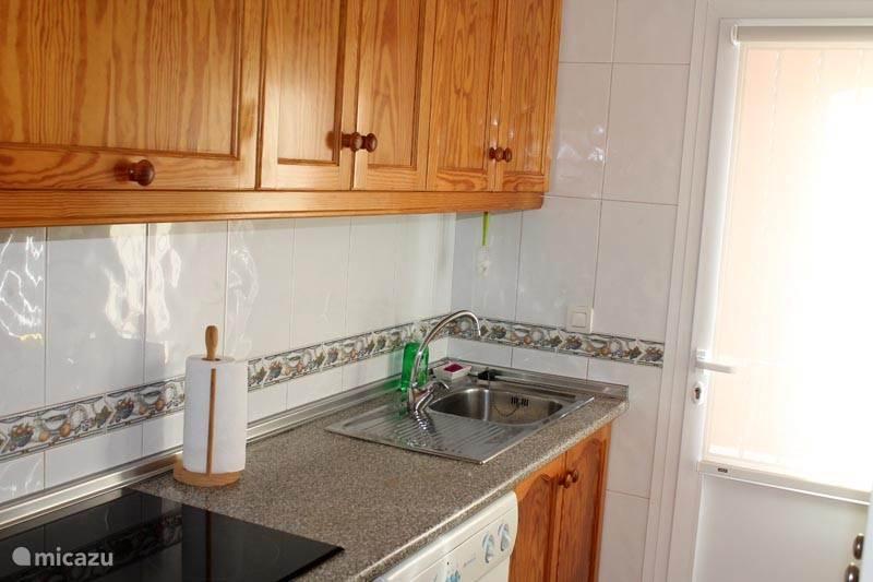 keramische kookplaat, wasmachine, deur naar buiten.