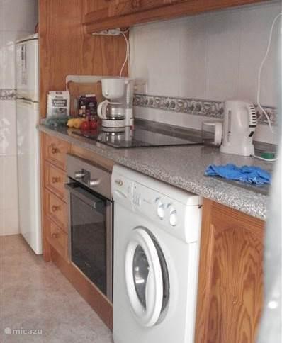 Keuken met koel/vriescombinatie en daarboven de boiler. Keramische kookplaat met daaronder combi oven.