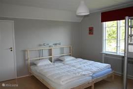 Deze slaapkamer heeft 2 1-persoonsbedden en een stapelbed. Alle bedden voorzien van dekbed en kussen. Op de kamer spiegel met kapplankjes en bedlampjes. Vanuit deze kamer is een kleine ruimte te bereiken waar een extra matras ligt. Leuk hok voor een jongere om te slapen.