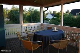 Op de zeer ruime veranda is het heerlijk toeven. Zijkanten zijn afgesloten met glas. Leuk uitzicht op zweeds heuvelland en prachtige zweedse avondlucht. Ruime eettafel met 6 rieten kuipstoeltjes. Stoeldekjes aanwezig.