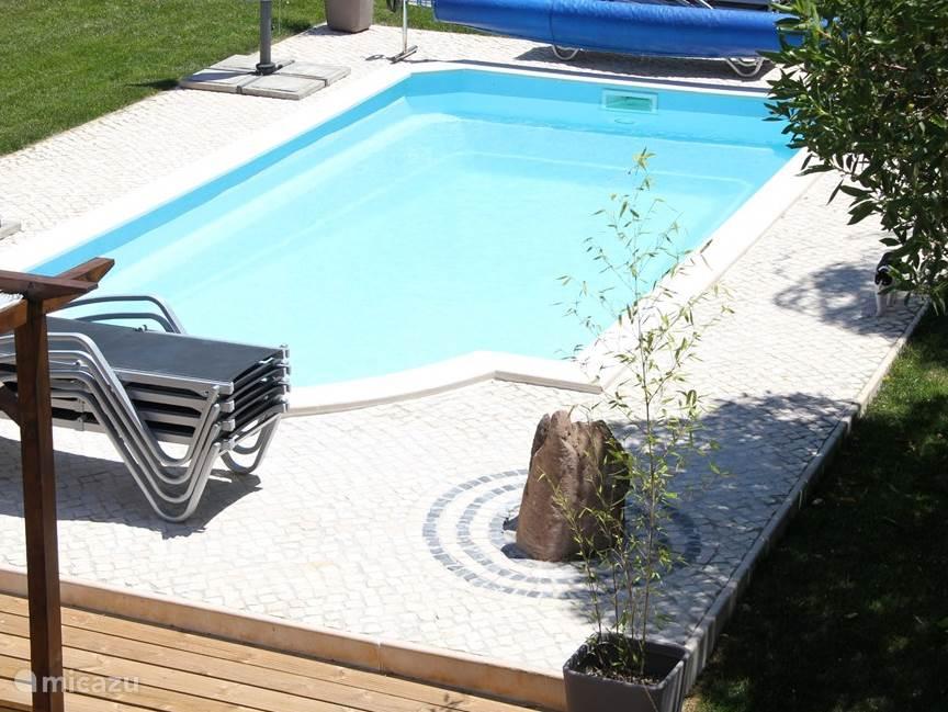 Gezamenlijk verwarmd zwembad met zentuin decoratie.