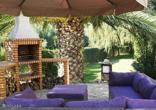 Ruim prive lounge terras met BBQ en uitzicht over tuin.
