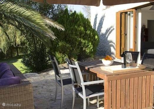Dubbelopenslaande deuren naar het ruime terras met lounge banken en eettafel en twee parasols.