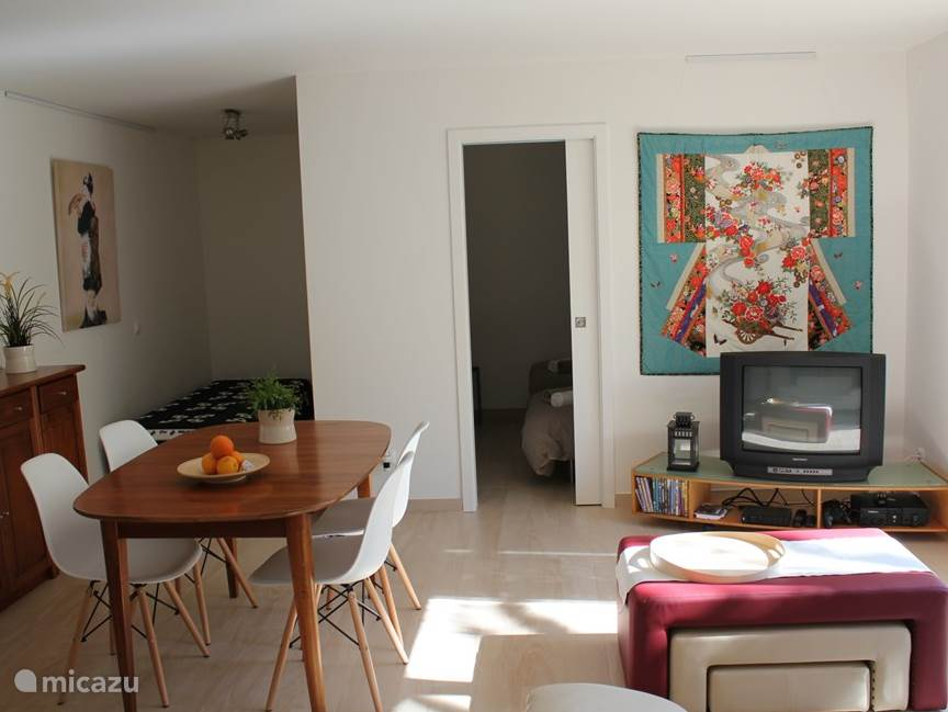 Woon-/eetkamer met extra bedbank in een nis van de kamer voor een 5e persoon.