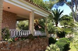 Een van de meerdere veranda's met uitzicht op de volgroeide tuin