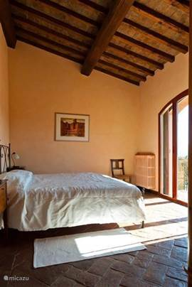 Slaapkamer 2 met heerlijke matrassen en openslaande deuren naar balkon. Met vergezichten over het Toscaanse landschap. Airconditioned.