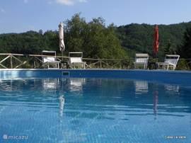 uitzicht vanaf het terras op het zwembad en de bergen van Umbrië