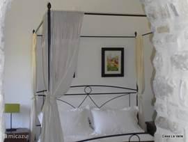 sfeervolle slaapkamer  met hemelbed en aangrenzende badkamer