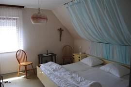 Slaapkamer op de eerste etage met king-size bed (2x2 meter).