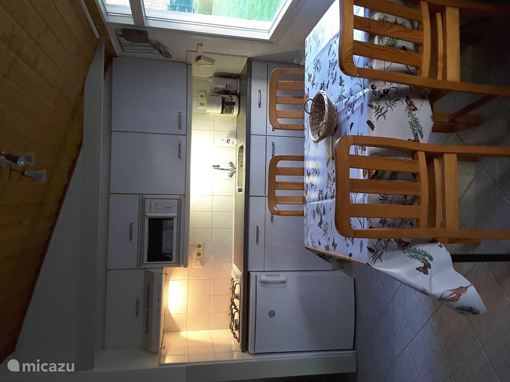 De open keuken voorzien van een koffiezetapparaat en een waterkoker, magnatron koelkast met vriesvakje en een losse grill/bak oven.een 4 pits gasfornuis en een eettafel met 4 stoelen(twee extra stoelen in slaapkamers)