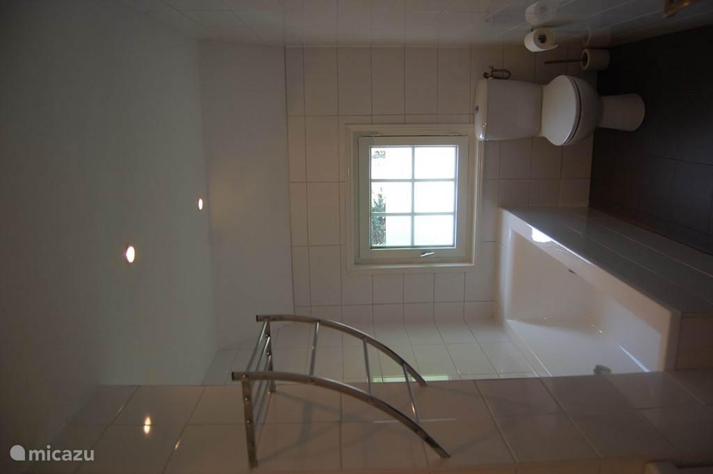 Badkamer met bad, wastafelmeubel en WC. Deze badkamer is in 2017 volledig gerenoveerd.