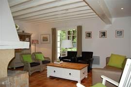 De ruime woonkamer met openslaande tuindeuren biedt 8 zitplaatsen en een openhaard. Hout wordt gratis ter beschikking gesteld. U beschikt over nederlandse TV middels sateliet, Wii spelcomputer en draadloos internet.