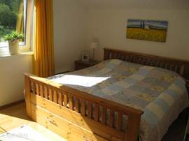 Spacious bedroom with door to balcony and own TV.