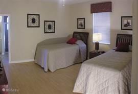 3e slaapkamer met 2 extra lange éénpersoonsbedden en eigen badkamer met douche en toilet.